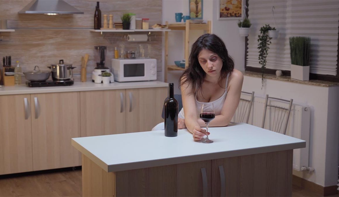 depressed woman drinking alone header
